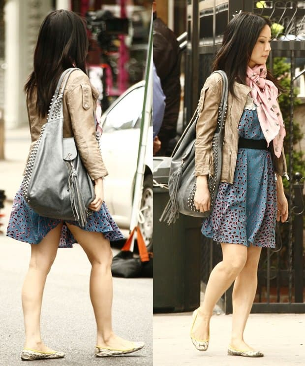 Lucy Liu in a bright blue and black printed dress with a beige bomber jacket