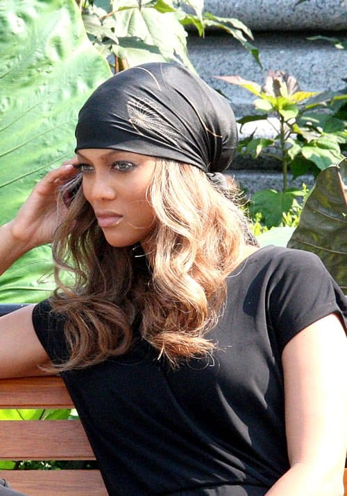 Tyra Banks wears a headscarf while talking on her cell phone