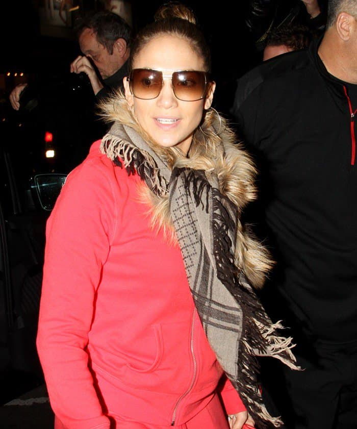 Jennifer Lopez in red tracksuit and scarf