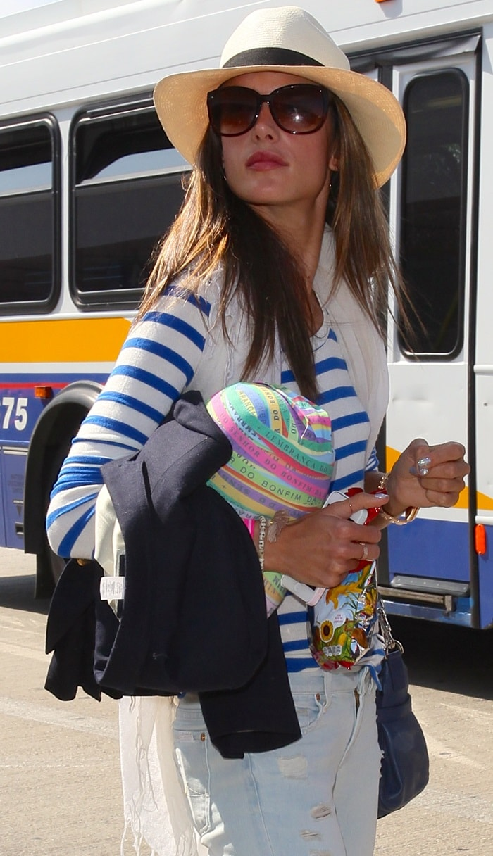 Alessandra Ambrosio rocks a Panama hat, uber cool sunnies, a blue purse, and a winter white scarf