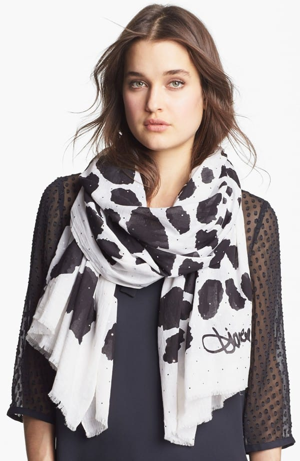 Bold spots splash across a classic fringed scarf embellished with tiny, silvery accents for a hint of sparkle and gleam