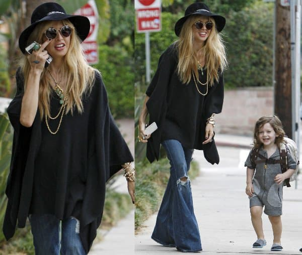 Showing already? Pregnant Rachel Zoe puts on a large poncho for her walk around town