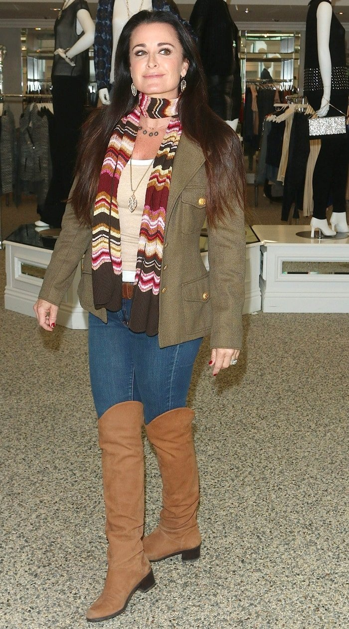Kyle Richards wears a colorful scarf withjeans and over-the-knee boots