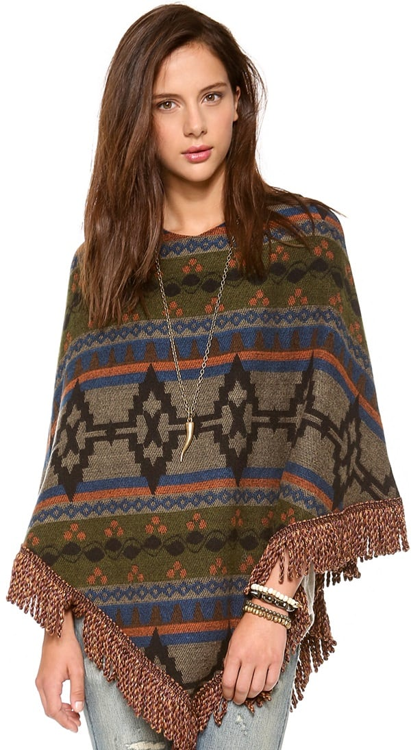 This poncho features a tribal-inspired pattern and cabled fringe at the hem