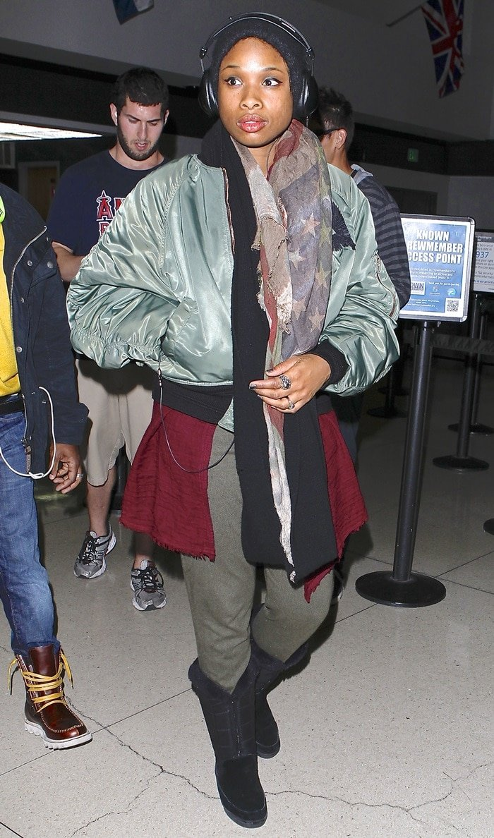 Jennifer Hudson wears several scarves with boots, a beanie, and a thick jacket