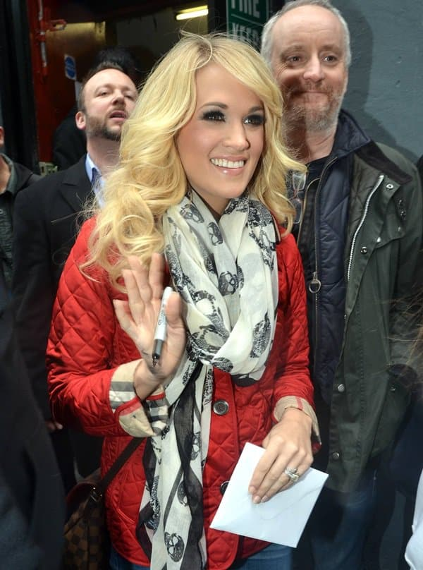 Carrie Underwood wears her classic white McQueen skull scarf with a bright red jacket as she signs autographs for fans while in Dublin, Ireland, on March 14, 2013