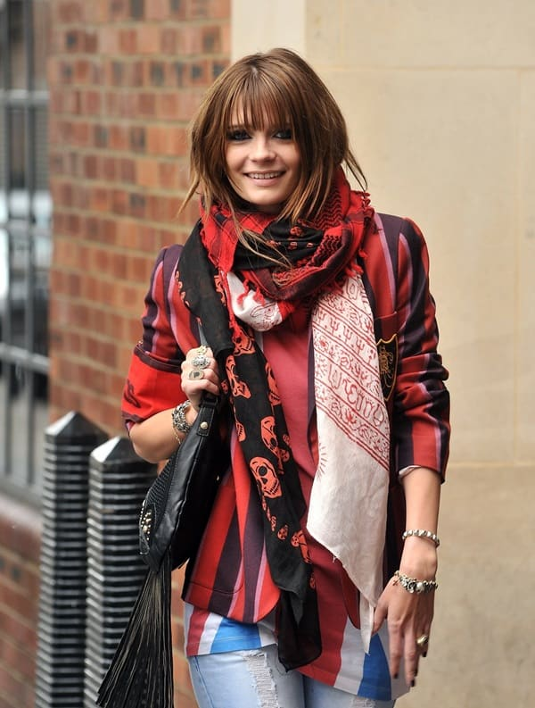 Mischa Barton poses for the photographers in a black Alexander McQueen scarf paired with a colored tee and an even more colorful blazer on April 21, 2009