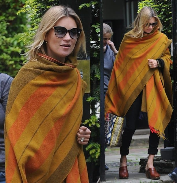 Kate Moss wearing a pair of clogs and a huge blanket topper while exiting her home in London