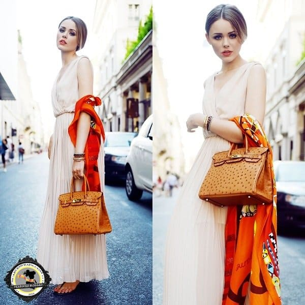 Kristina Bazan of Kayture decorates her dress by wearing a bright scarf and handbag at the crook of her arm