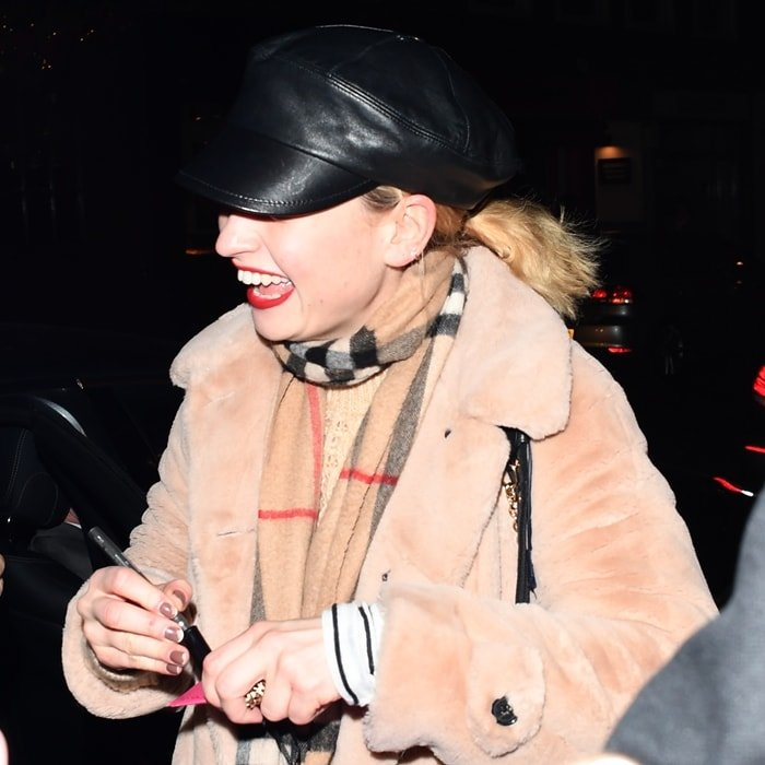 Lily James wears her favorite Burberry scarf with a black baker boy style cap